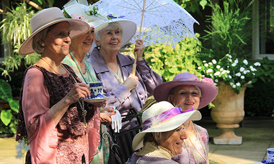Five ladies pose for a picture recreating teatime in a garden